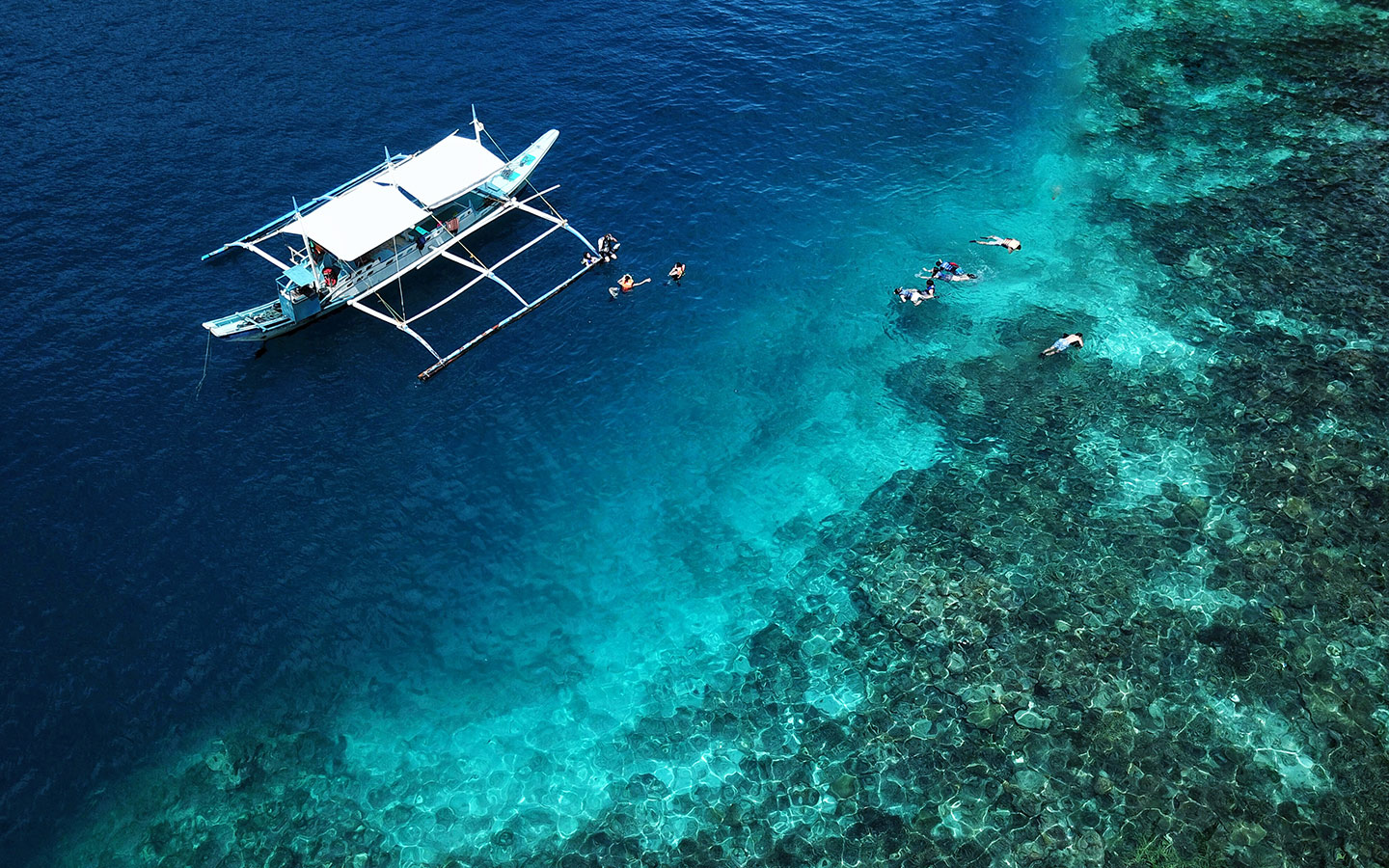group snorkeling in crystal clear reef as traditional banca boat waits in anchor