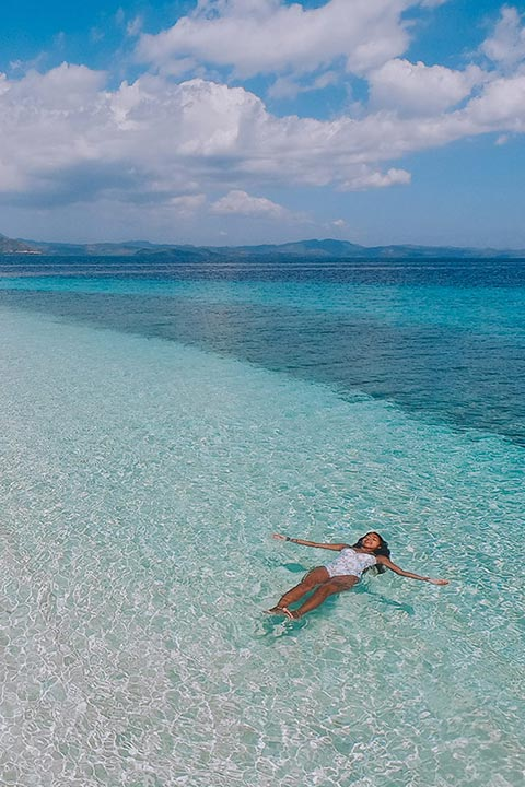 Women sunbathing crystal clear Taytay Bay waters
